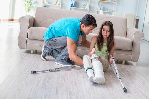 парень помогает девушке подняться на костылях